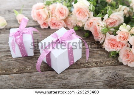 Bouquet of pink roses and gift on a wooden background - stock photo