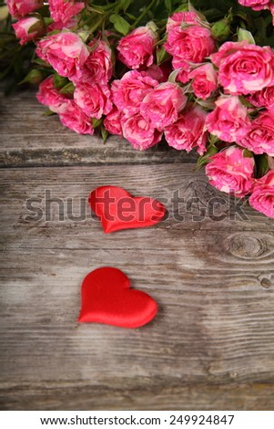 Bouquet of pink roses and hearts on a wooden background