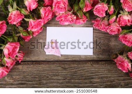 Bouquet of pink roses, heart  and greeting card on a wooden background