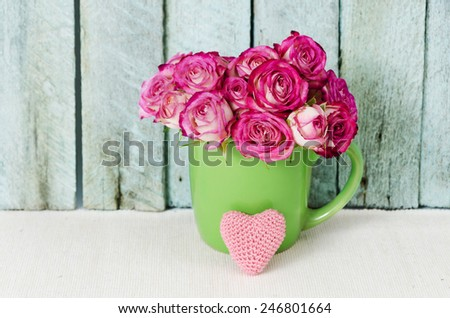 bouquet of pink roses in a cup against vintage wooden panels - stock photo
