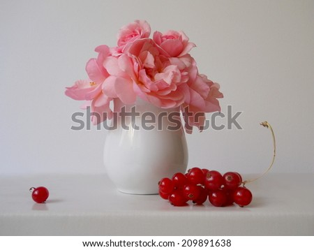 Bouquet of pink roses in a vase and red currants. - stock photo