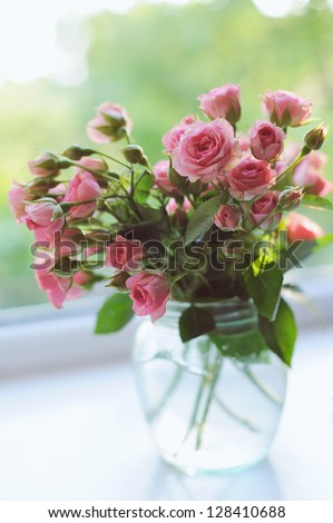 Bouquet of pink roses in vase on the window in the sunshine - stock photo