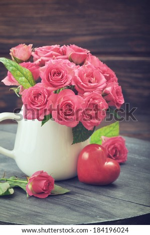 Bouquet of pink roses in vase with stone heart on wooden background - stock photo