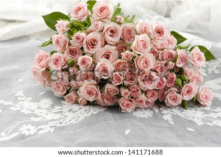 Bouquet of pink roses on silk - stock photo
