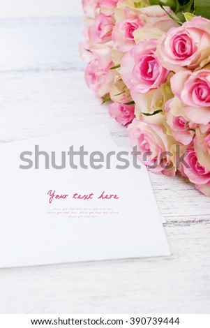 Bouquet of pink roses with blue ribbon for present on a vintage wooden background, copy space, closeup, selective focus - stock photo