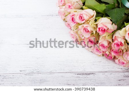 Bouquet of pink roses with blue ribbon for present on a vintage wooden background, top view - stock photo