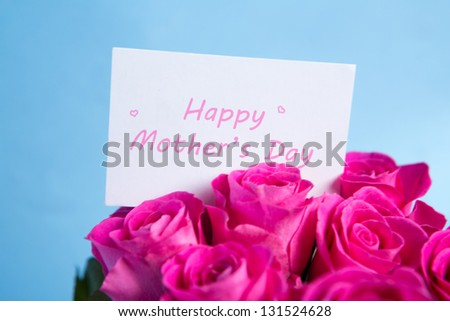 Bouquet of pink roses with mothers day card on blue background - stock photo