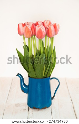 bouquet of pink tulips in an old blue jug on a white wooden table - stock photo