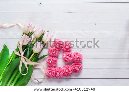 Bouquet of pink tulips with pink ribbon and heart shape on white painted wooden background and empty space for text. Top view with copy space - stock photo