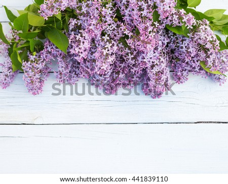 Bouquet of purple lilacs flowers on a light blue shabby wooden background. Vintage floral background with spring flowers. Copy space - stock photo