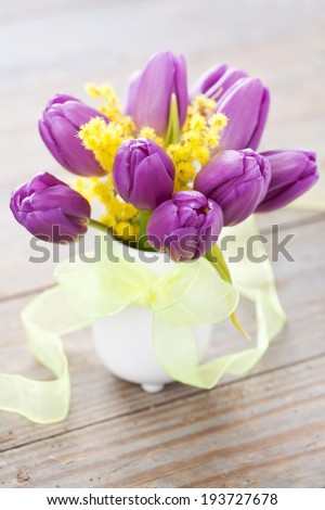 Bouquet of purple tulips and mimosa in vase on wooden background - stock photo