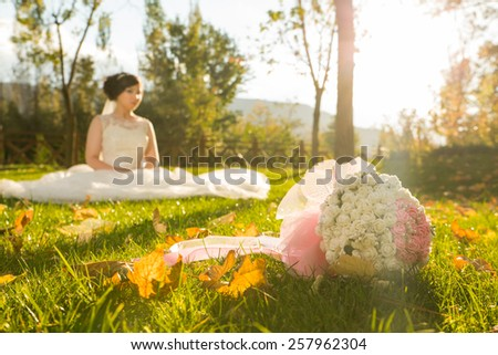Bouquet of red flowers on the grass and a wedding couple in blur background - stock photo