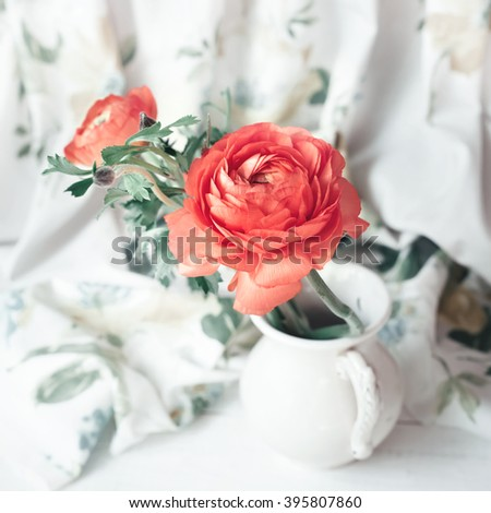 Bouquet of red ranunculus in old vase, closeup shot. Vintage toned photo. - stock photo