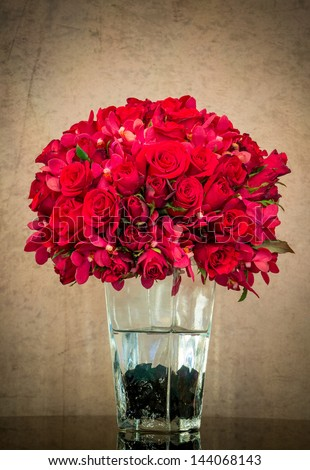 Bouquet of red rose in glass vase on grunge background