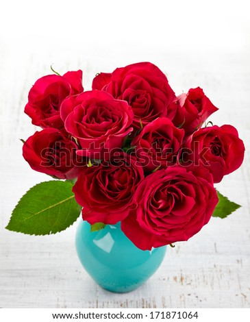 Bouquet of red roses in a vase on white wooden background - stock photo