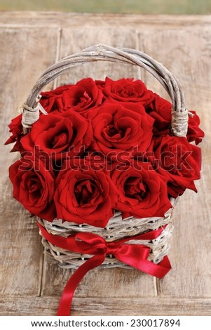 Bouquet of red roses in wicker basket - stock photo