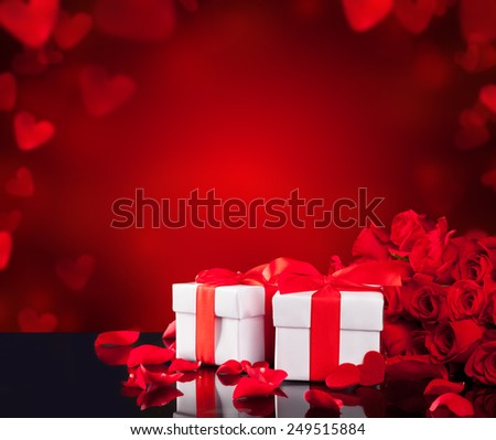 Bouquet of red roses on black glass table with two gifts and abstract blur background with copy-space for text - stock photo