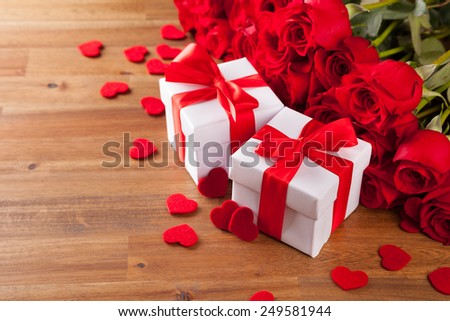 Bouquet of red roses on wooden table with two gifts. - stock photo