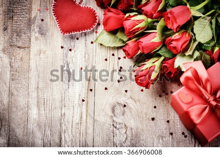 Bouquet of red roses with decorative heart and present. St Valentine's concept with copy space - stock photo