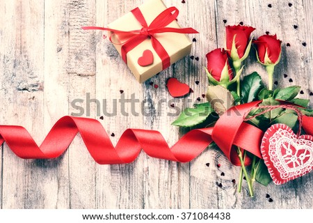 Bouquet of red roses with decorative hearts and presents. St Valentine's concept with copy space