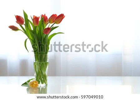Bouquet of red tulips in a glass vase on a glass table