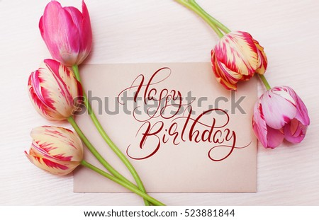 Bouquet of red tulips on white background with text Happy Birthday. Calligraphy lettering