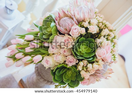 Bouquet of roses and tulips stands in an old vase - stock photo