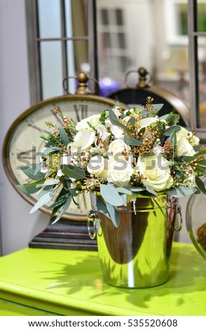 Bouquet of roses in a shiny metal bucket on a green table on the background of mirrors and clocks.