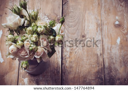 Bouquet of roses in metal pot on the wooden background, vintage style - stock photo
