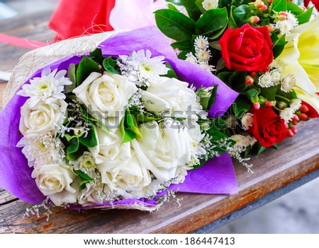 bouquet of roses left abandoned on wooden table