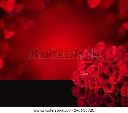 Bouquet of roses on black glass table, copy-space on abstract blur background - stock photo