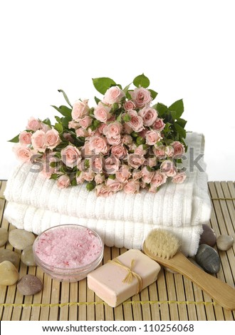 Bouquet of roses on towel with soap and salt in bowl on mat background - stock photo