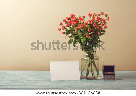 Bouquet of roses with blank greeting card and vintage jewelry box on the wooden table - stock photo