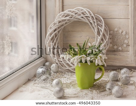 Bouquet of snowdrops and Christmas-tree toy (product of mass production) in the window