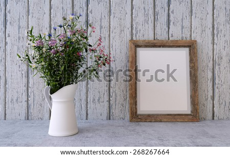 Bouquet of spring field flowers in a vase on a white vintage wooden board home decor in a rustic style with frame - stock photo