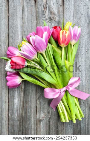 bouquet of spring tulips on old wooden background - stock photo