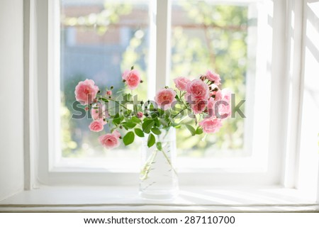 Bouquet of summer roses in glass vase near the window  - stock photo