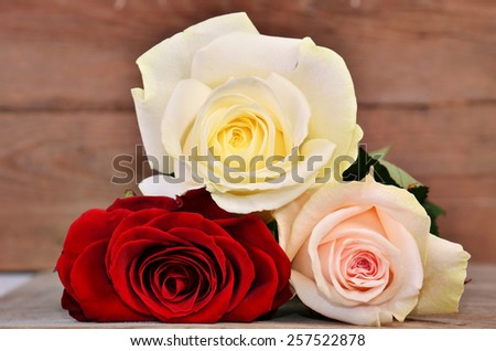 Bouquet of three roses lying on a wooden surface - stock photo