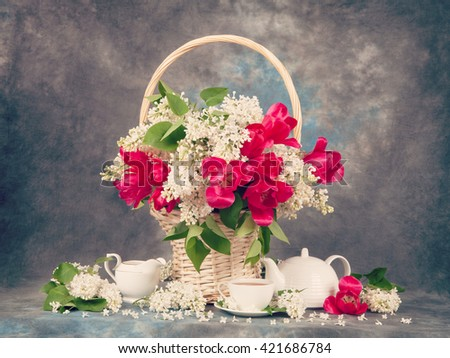 Bouquet of tulip with lilac and tea cups on the table. Retro hipster version. - stock photo
