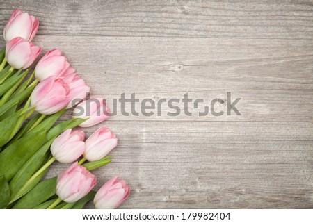 bouquet of tulips (border design) on wood table - stock photo