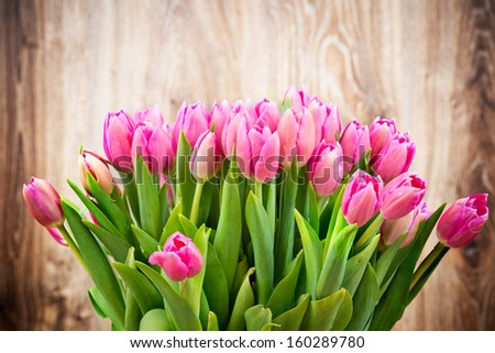 Bouquet of tulips on wooden background - stock photo