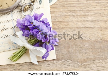 Bouquet of violet flowers (viola odorata) and vintage letters, copy space - stock photo