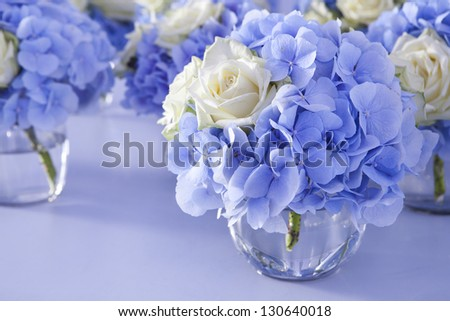 Bouquet of white and blue flower in vase of glass. Decoration of dining table. - stock photo