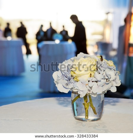 Bouquet of white and blue flower in vase of glass. Decoration of dining table. Silhouette people on background - stock photo