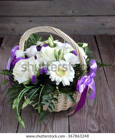 Bouquet of white  eustoma, roses and chrysanthemums in basket - stock photo