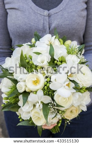 Bouquet of white flowers: ranunculus, freesia and orchid.