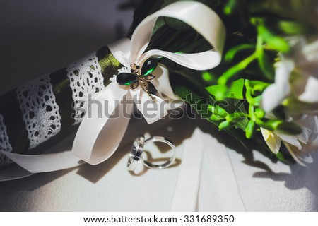 bouquet of white freesia with a white ribbon   and a pair of wedding rings - stock photo