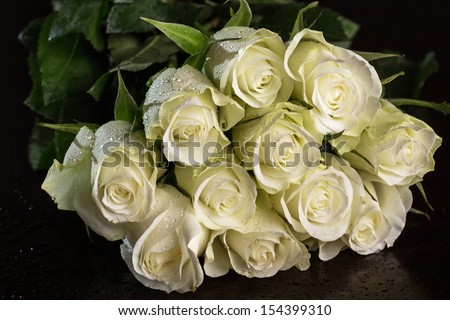 Bouquet of white roses over dark background