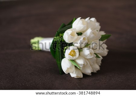 Bouquet of white tulips on a brown textile background. Side view.