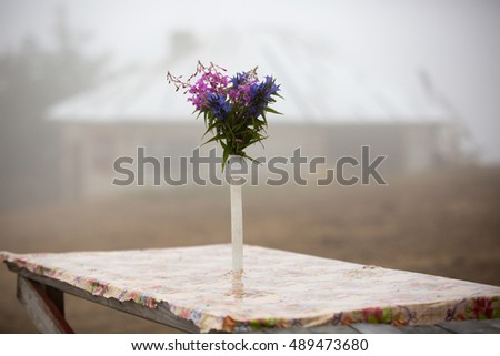 Bouquet of wild flowers on a rural wooden table on background of fog